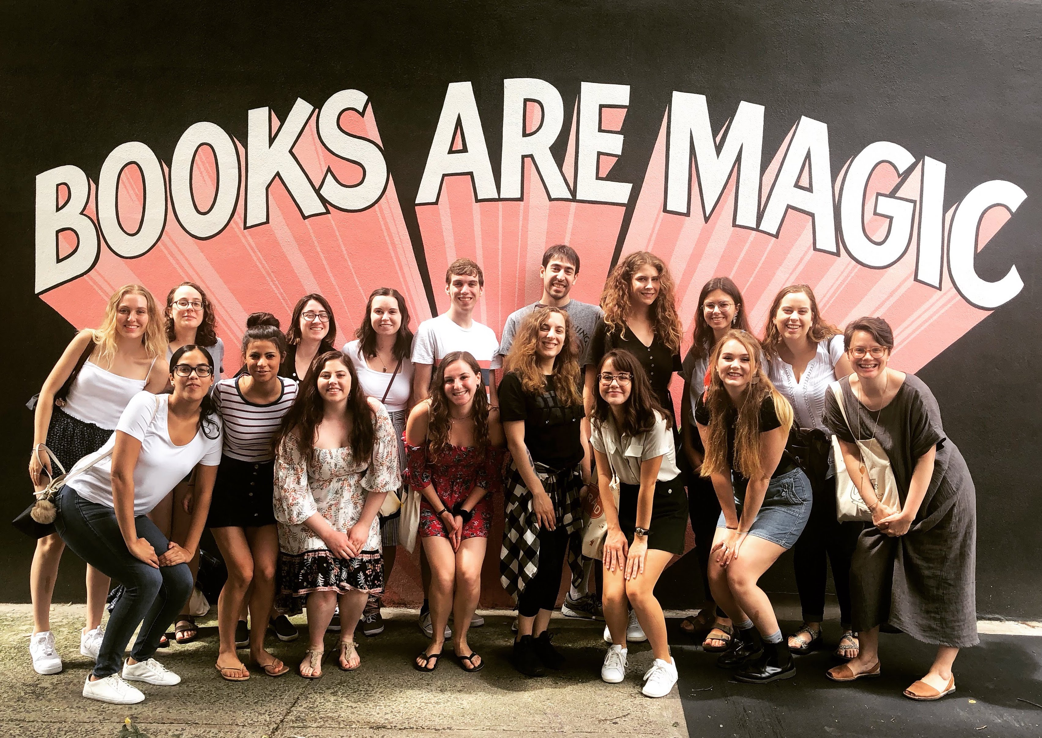 Students pose in front of the mural at Books Are Magic in Brooklyn.